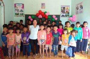 Cô giáo B'Lao (áo trắng) đứng trên đôi chân co quắp cùng các học trò. Ảnh: Việt Hiến